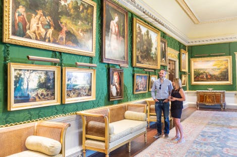 A young couple look at paintings in the Throne Room. The walls are lined with green silk damask and the paintings are hung in gold frames. A large rug covers the floor.