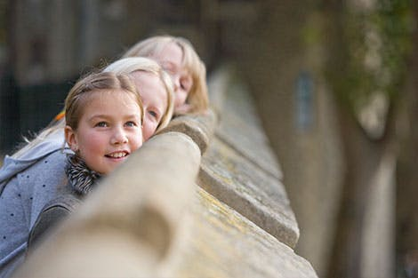 A young girl looks in amazement from the stone Battlements at the Tower of London