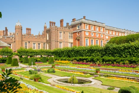 The Pond Gardens at Hampton Court Palace, showing bright planting and baroque architecture under a clear blue sky