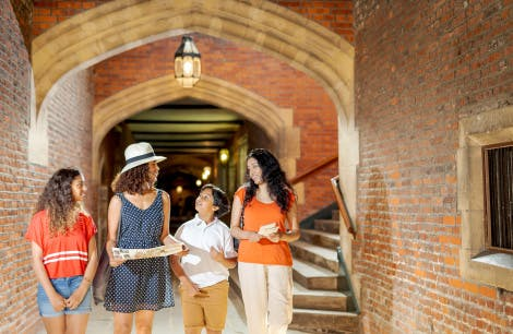 A family of two women, a boy and a girl look around them in Base Court of Hampton Court Palace