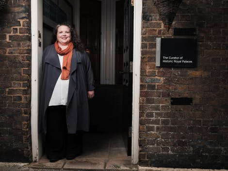 A member of Historic Royal Palaces staff stands in the doorway of a period building. There is a sign saying 'The Curator of Historic Royal Palaces' on the wall to the right