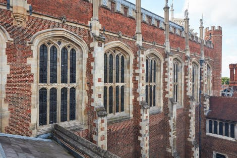 The red brick Tudor exterior of the Great Hall at Hampton Court Palace. Large stained-glass windows can be seen within the walls and brick supports jut out of the side of the exterior wall