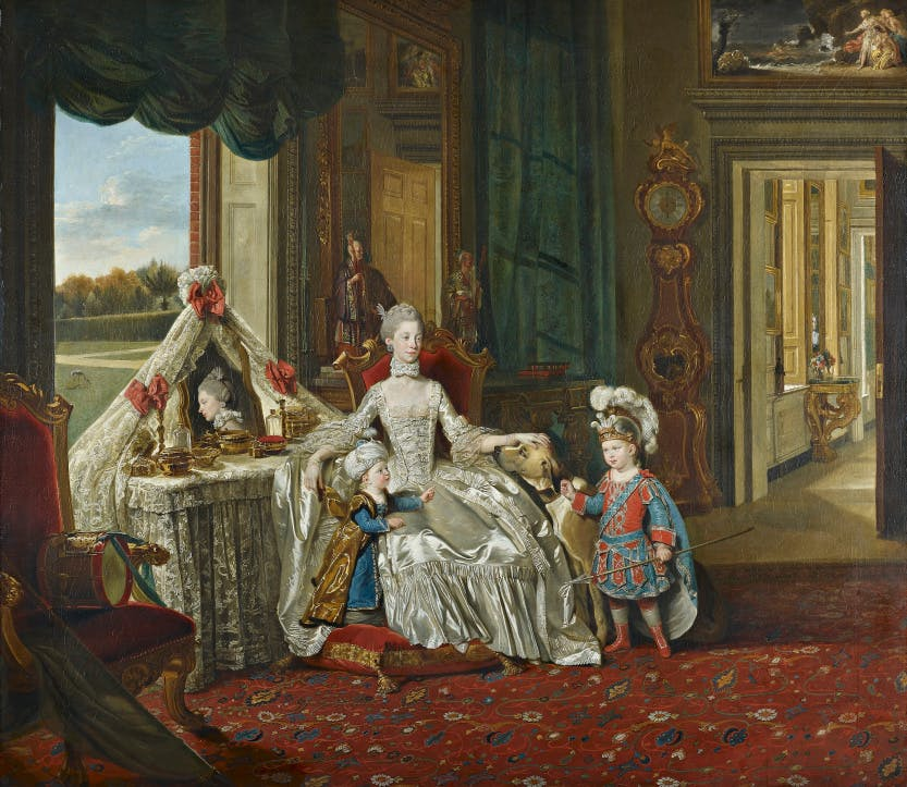 Queen Charlotte in a palace with her two eldest sons, with a window behind them and a view of the grounds.  In this domestic, dressing-room scene, Queen Charlotte sits at her toilette table in Buckingham House, overlooking the garden, and entertains her two eldest sons. Buckingham House had been acquired by George III just a few years before as a semi-private residence away from the business of the court, which at that time was based at St James's Palace. Contemporary accounts of George III and Queen Charlotte's daily routines allow us to reconstruct the scene.