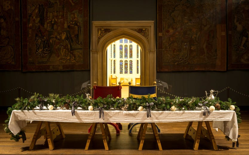 Christmas holly and foliage on the main table in the Great Hall at Hampton Court Palace, surrounded by Tudor tapestries