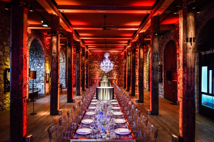 Long table set up for dinner in the Tower of London under red lighting and old medieval beam ceiling