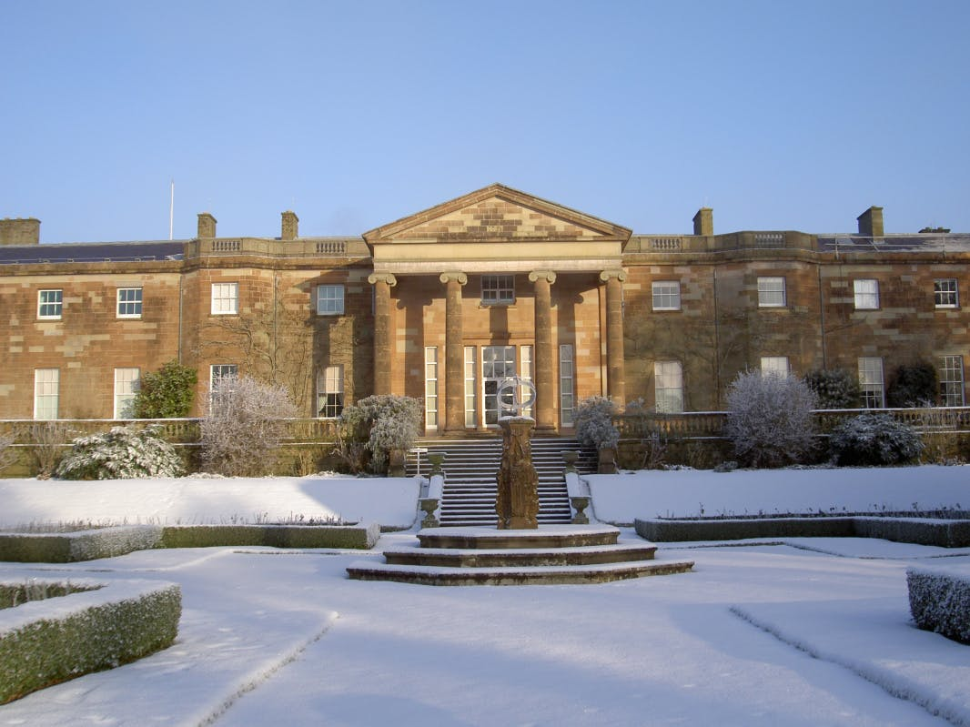 Rear view of the exterior of Hillsborough Castle in the snow, with blue skies and surrounding gardens.