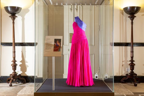 A long, bright pink and purple dress in a display case in a bright corridor at Kensington Palace. Two lamps are lit on either side of the case and a display stand is placed in the foreground
