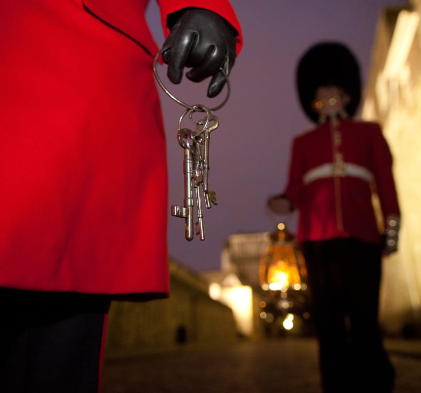 A close up image of a Yeoman Warden carrying a set of keys for the Ceremony of the Keys.  A guardsman stands in the distance holding a lamp.
