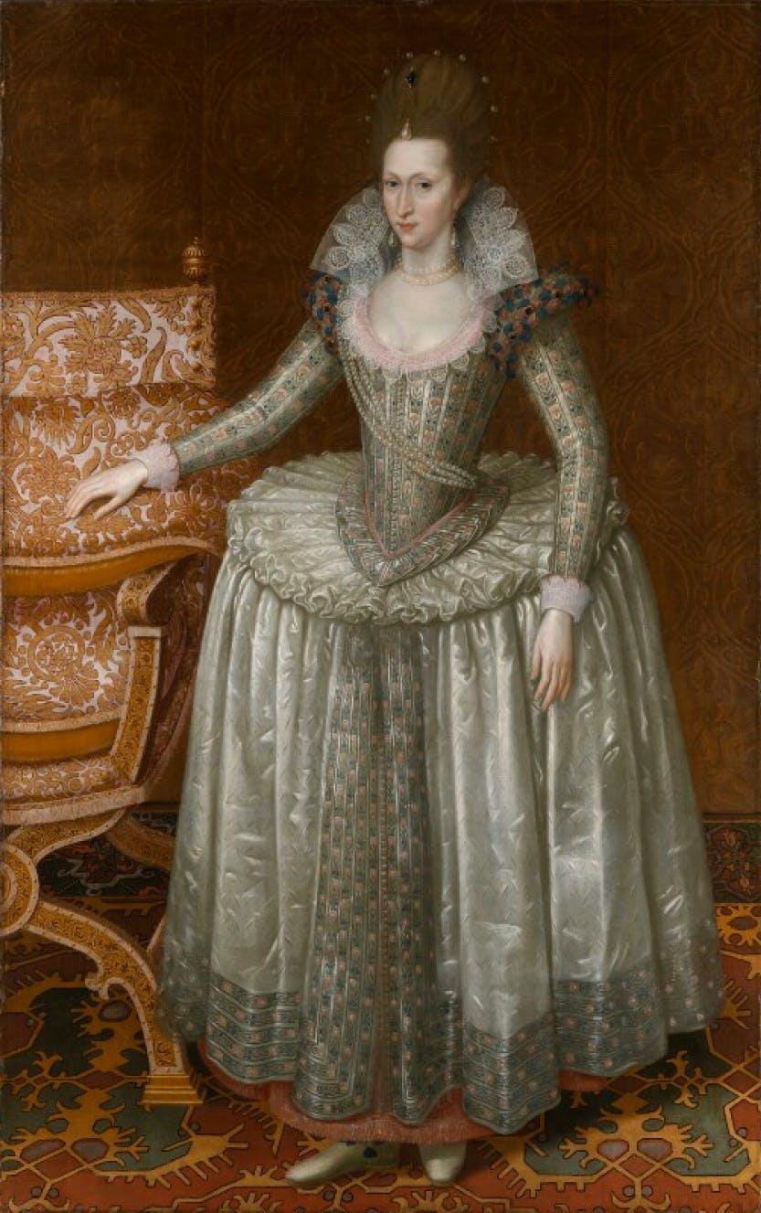 A portrait of Anne of Denmark wearing an elaborate dress with her hand resting on a chair.