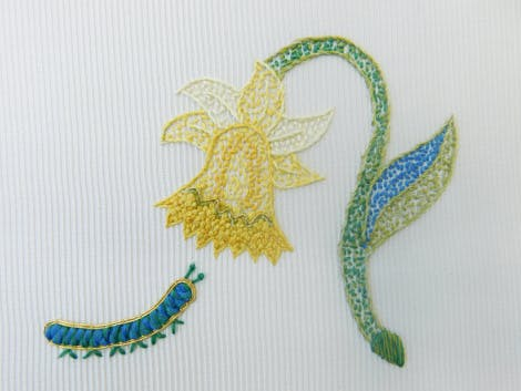 Embroidered daffodil and caterpillar on a white background