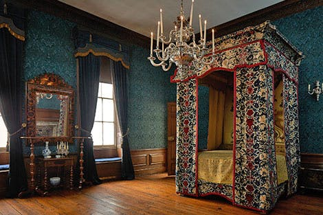 A large four poster bed covered in detailed period fabric, in a bedroom covered in dark green wall decor