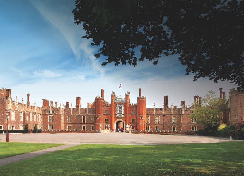 The west front of Hampton Court Palace with the gardens in the foreground under a blue sky.