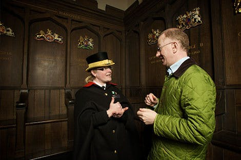 A member of Tower of London staff signs to a visitor