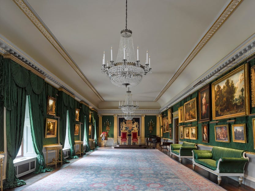 The Throne Room at Hillsborough Castle, with rich paintings on the walls and two red thrones at the end of the room.