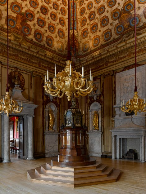 The Cupola Room, looking south east, showing William Kent's painted decoration of the walls and ceiling and an 18th-century musical clock the 'Temple of the Four Great Monarchies of the World' This room was the principal state room of the palace. It was here that Princess Victoria (later Queen) was christened in 1819