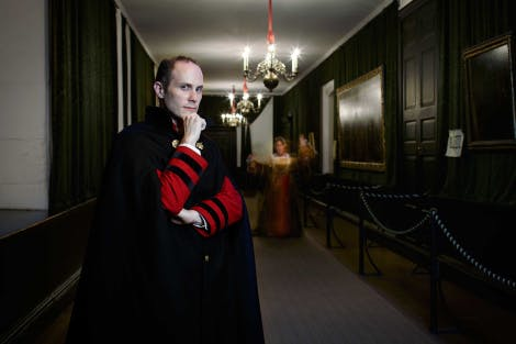 A tour guide stands in the Haunted Gallery of Hampton Court Palace as ghostly figures move in the background