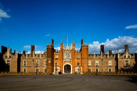 The red brick Tudor front of Hampton Court Palace under a bright blue sky