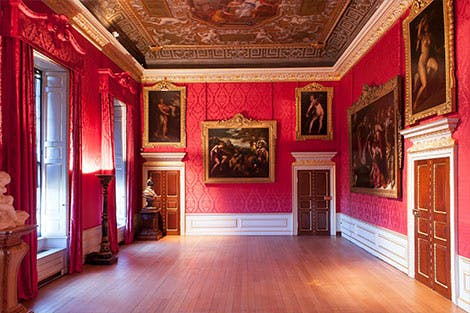 The bright red walls and hanging art in the King's Gallery at Kensington Palace