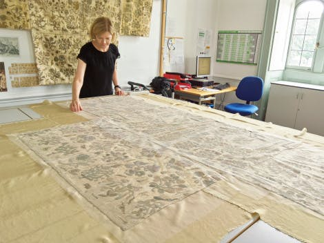 A conservator tends to the Bacton Altar Cloth as it rests on a table in a bright studio. A replica of the cloth hangs on the wall behind