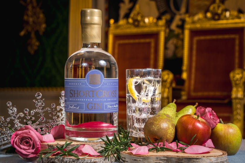 A still life shot of a bottle of Hillsborough Gin, surrounded by apples, pears and roses which are the flavours of the alcohol. A sparkly tiara and chairs upholstered with rich red fabric suggest a regal location.