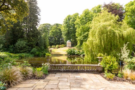 Lady Alice's Temple, looking west across the terrace and pond.   This domed temple was given as a wedding gift to Lady Alice Hill by her brother, the 5th Marquess of Downshire in 1867. A circular seat inside the temple sits behind a screen of Ionic columns.