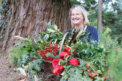 Florist Lorna Borwnlee (HRP staff member) with cinnamon sticks, cones, dried oranges along with gathered red berries, feathers, red ribbon and Christmas foliage in a basket; collected from the Hillsborough Castle gardens.