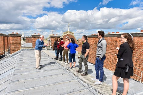 A tour guide addresses a group on a rooftop tour at Hampton Court Palace