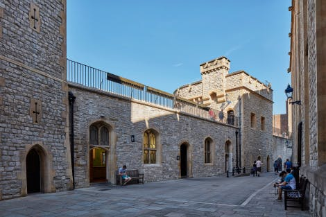The men's entrance to the Brick Tower Toilets after conservation in 2016, looking north-east towards the Brick Tower. Visitors to the Tower of London are seen walking along and sitting on benches.
