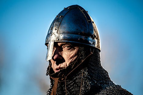 An actor dressed as a medieval soldier in armour