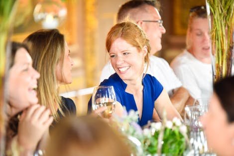 Guests talk at dinner in a panelled room