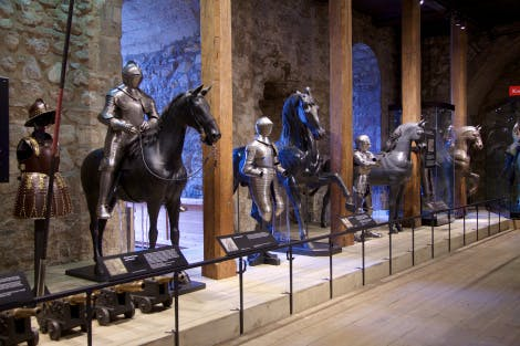 A row of suits of armour and wooden horses statues in the Line of Kings exhibition in the White Tower of the Tower of London.