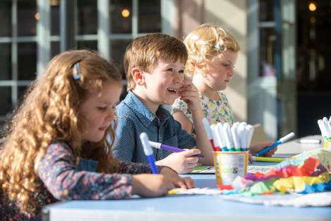 Children smile as they colour and draw during family activities in the Stableyard cafe courtyard of Hillsborough Castle and Gardens