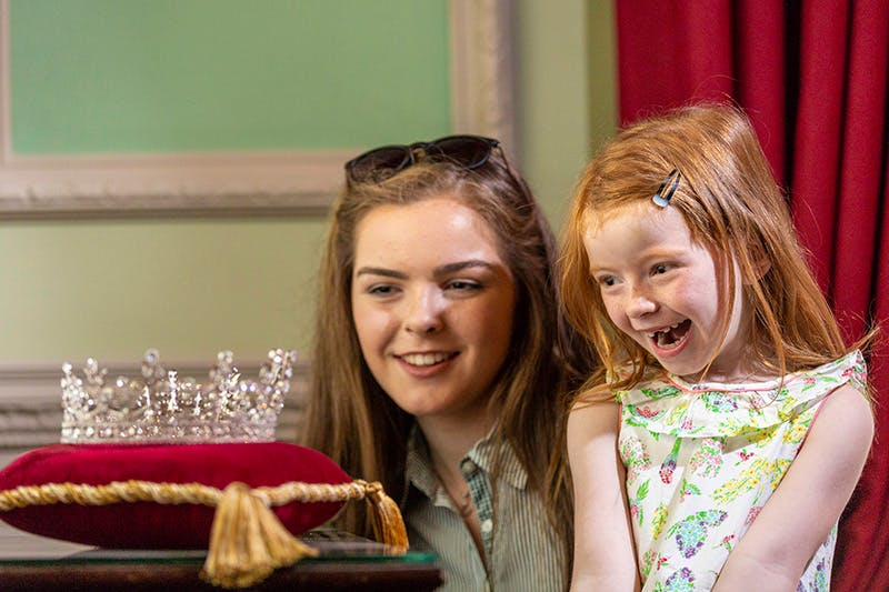 A young teenage girl and her younger sister smile with delight as they look at a replica of a tiara worn by HM The Queen in 1953 during her first ever visit to Hillsborough Castle. The tiara sits on a red velvet cushion with gold trim and is located in the State Dining Room.