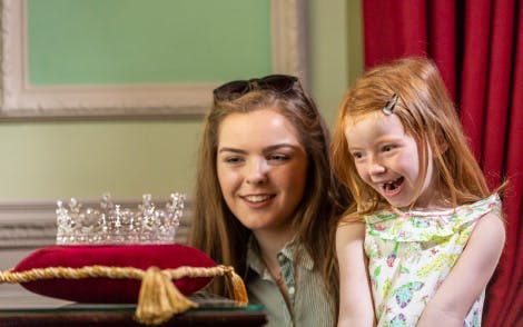 A young teenage girl and her younger sister smile with delight as they look at a replica of a tiara worn by HM The Queen in 1953 during her first ever visit to Hillsborough Castle. The tiara sits on a red velvet cushion with gold trim and is located in the State Dining Room. Green walls and a deep red curtain is visible behind the young girls.