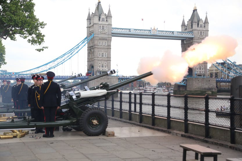 Canon firing in gun salute on Tower Wharf, captured during the firing, with soldiers flanking the canon