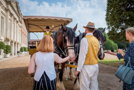 Visitors meet the Shire Horses in the East Front Gardens at Hampton Court Palace. The baroque palace can be seen in the background