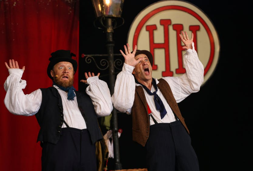 Two actors dressed in historical costume throw up their hands in horror as part of a Horrible Histories performance. The Horrible Histories logo appears in the background as part of the set.