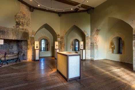 The Imprisonment at the Tower exhibition in the Beauchamp Tower at the Tower of London, showing three arches in the wall, a fireplace on the left hand side and a display case in the centre of the room