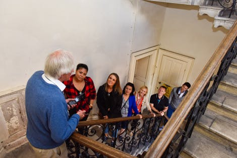 A guide talks to a tour group on the stairs at Hampton Court Palace