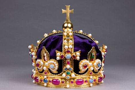 A gold and purple recreation of Henry VIII's crown on a grey background