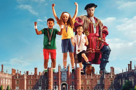 Henry VIII standing on the Tudor west front of Hampton Court Palace, alongside a group of children in sporting clothing