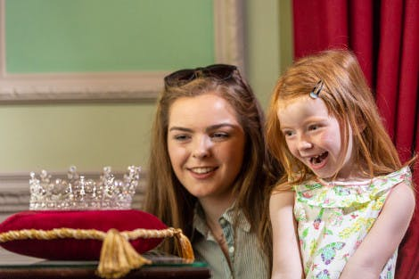 Two young girls look at a replica of a diamond silver tiara on a red display pillow in a historic room.