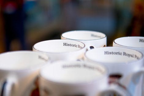 A group of Historic Royal Palaces mugs line a shelf in the Palace Shop