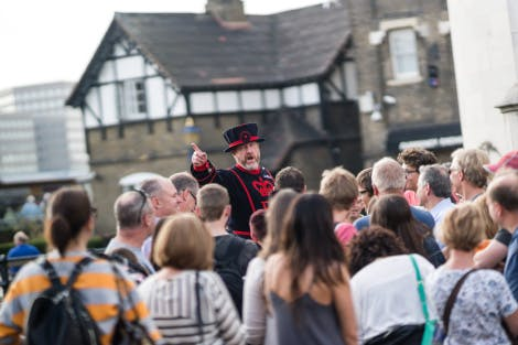 A Yeoman Warder talks to a crowd of visitors and points to the Tower of London as he begins his tour at on the Causeway