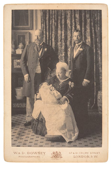 A photograph of Queen Victoria (1819-1901) with her son Edward (1841-1910), later King Edward VII, her grandson George (1865-1936), later King George V, and her great-grandson Edward (1894-1972), later Edward VIII and then the Duke of Windsor. The Queen is seated holding her great grandson and her grandson and son stand behind. The name of the photographer is printed on the bottom of the photograph, 'W & D Downey Photographers'.  This photograph is part of the contents of a photograph album.