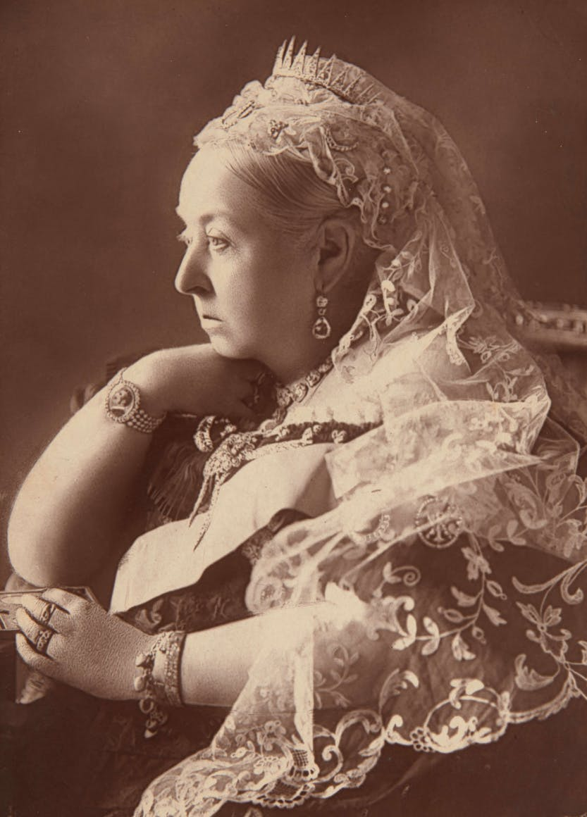 Half-length seated portrait of Queen Victoria.  The Queen wears a white veil and crown and a bracelet with a portrait of Prince Albert