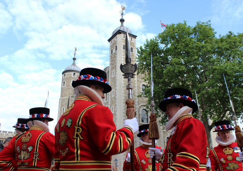 Yeoman Warders wearing their bright red ceremonial state dress uniforms standing in front of White Tower. They are standing in line and performing a historic ceremony called the Beating of the Bounds..