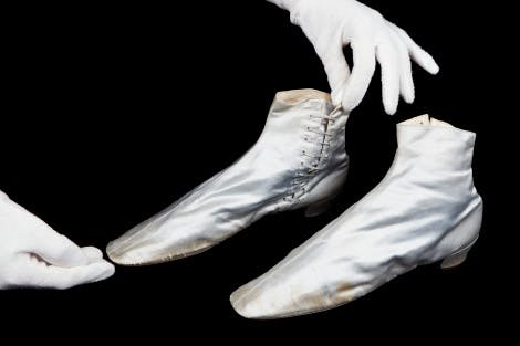 A pair of silver boots in a Victorian style on a black background. A pair of hands in white gloves attend to the boots