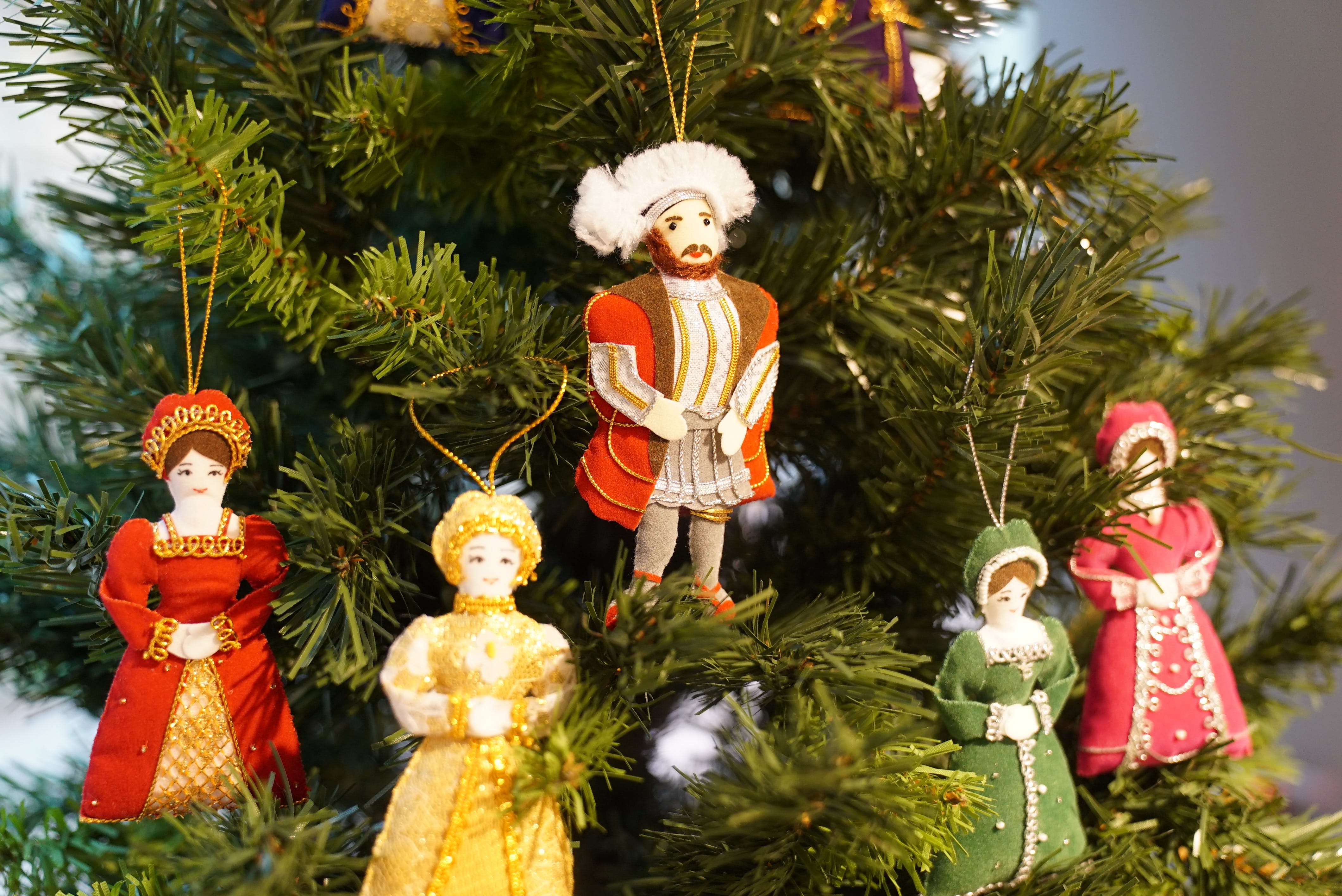 A selection of Christmas tree figure decorations including Henry VIII hanging on a Christmas tree.