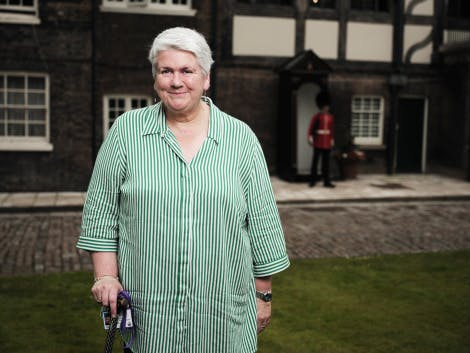 A member of Historic Royal palaces staff stands on Tower Green surrounded by the Tudor buildings of the Queen's House at the Tower of London. A guard can be seen in the background